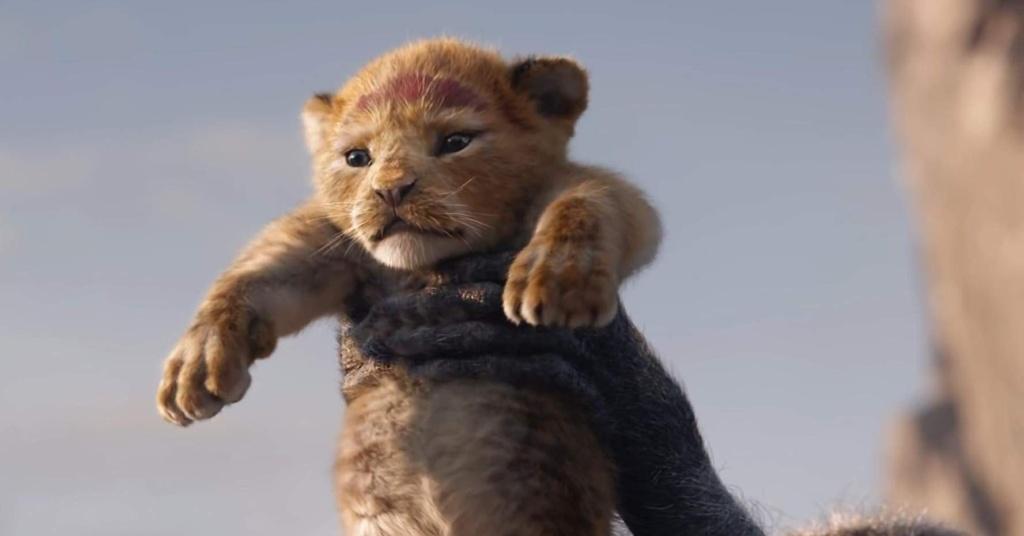 Simba, de niño, en las manos de Rafiki, el mono. Ambos en formato live-action.