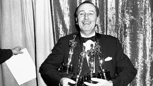 Walt Disney, sonrisa de oreja a oreja y con las manos llenas de estatuillas.