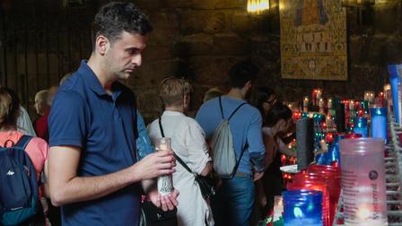 Hombre en una iglesia llena de gente con una vela encendida en sus  manos.