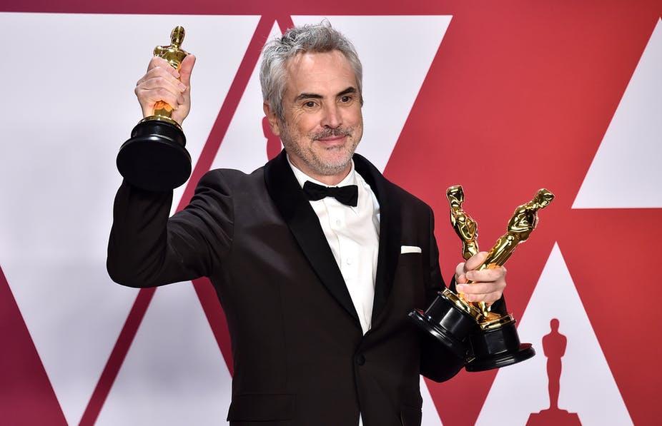 """Alfonso Cuarón, director de """"Roma"""" con sus tres Oscars en la mano, en la celebración de los Oscars 2019, donde Netflix pisó bastante fuerte."""