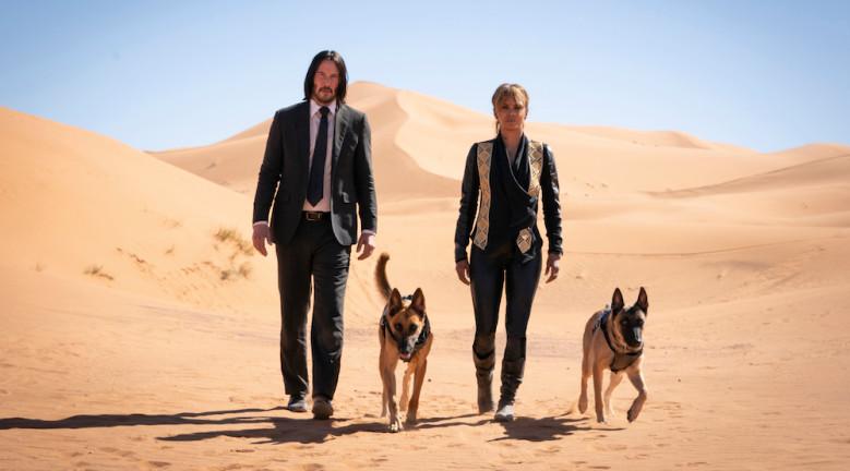 John y el personaje de Halle Berry en el desierto junto a dos perros